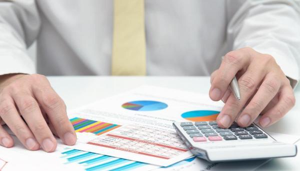 businessman-using-calculator-and-graphs.jpg